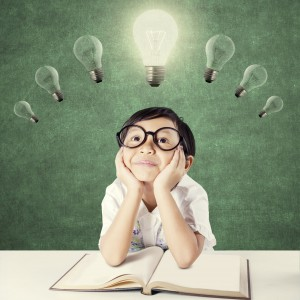 42878708 - attractive female elementary school student with a textbook on the table, thinking idea while looking up at bright light bulb